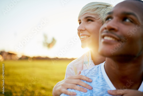 Foto  Mixed race couple of millennial in a grass field embracing for a