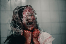 A Woman Is Brutally Murdered By A Bag Over Her Head. Feeling Tortured And Needing Help, Halloween Murder Concept.