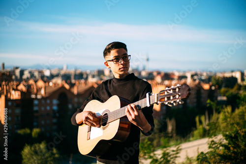 Young boy playing guitar in the city of Madrid, Spain in the background. - 296406488