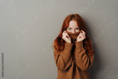 Foto Playful young woman hiding inside her collar