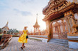 Leinwanddruck Bild - Travel by Asia. Young woman in hat and yellow dress walking near the Chalong buddhist temple on Phuket Island in Thailand.