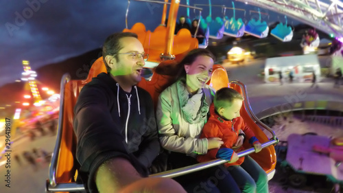 Valokuva Parents and child having fun in amusement park, night entertainment