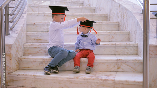 Fotografie, Obraz  Two children sit on stairs, big brother arrange graduation cap to baby brother