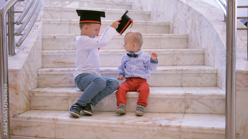 Obraz na plátně  Brothers graduation, big kid putting the hat on little child