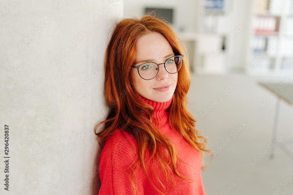 Fototapeta Thoughtful young woman wearing glasses