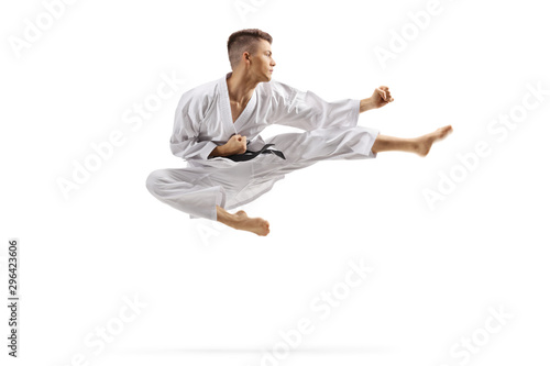 Young man in karate kimono jumping and kicking