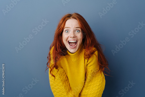 Laughing delighted young woman leaning forwards Canvas Print