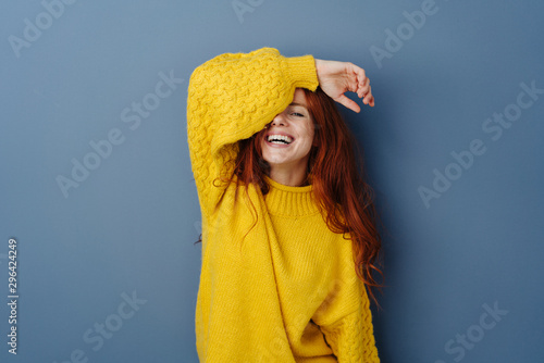 Laughing playful young woman covering an eye Canvas Print