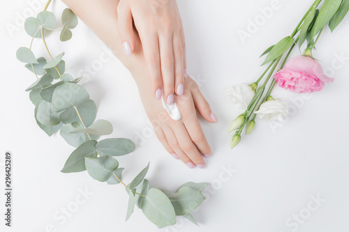 Poster Spa Close-up beautiful sophisticated female hands with pink flowers on white background. Concept care, anti-wrinkles, anti-aging cream, spa