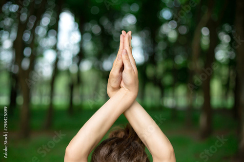 A young sports girl practices yoga in a quit green summer forest, yoga assans posture. Meditation and unity with nature