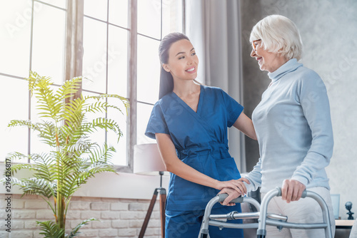 Young female social worker helping senior woman to walk with walker at home Wallpaper Mural