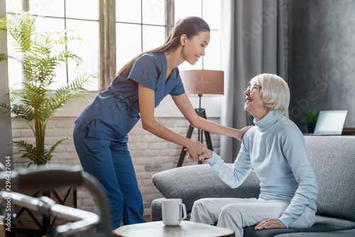 Fotografía Happy female professional caregiver taking care of elderly woman at home
