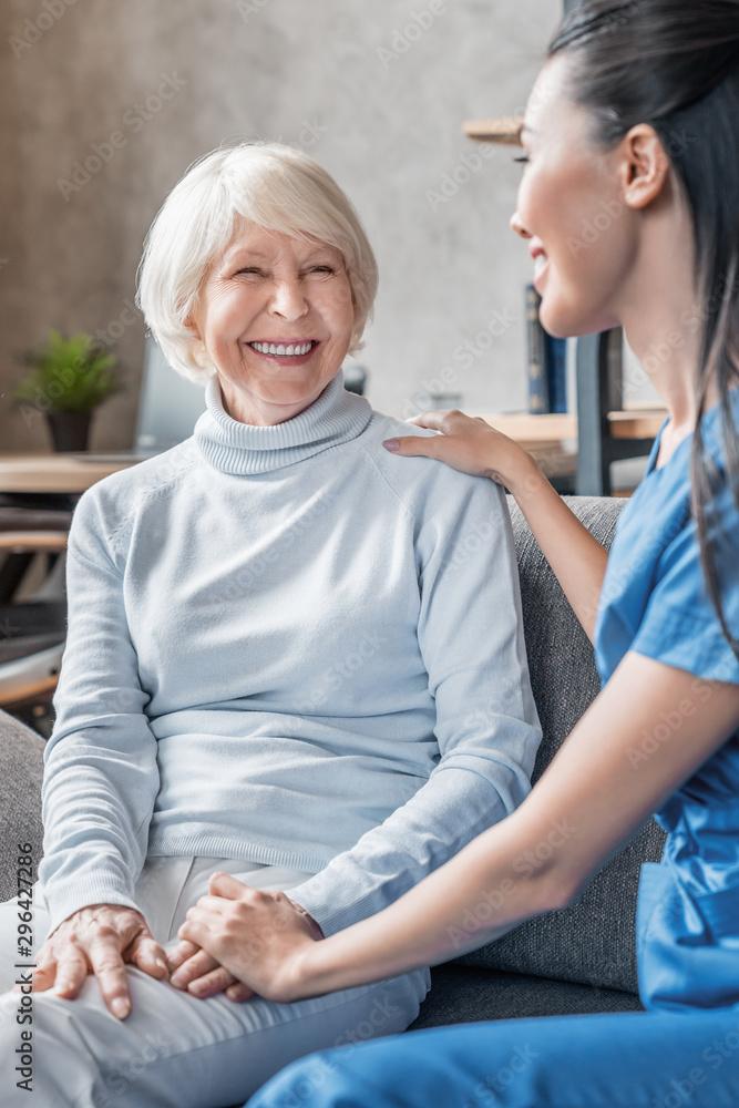 Fototapeta Vertical shot of helpful nurse taking care of senior woman in nursing home