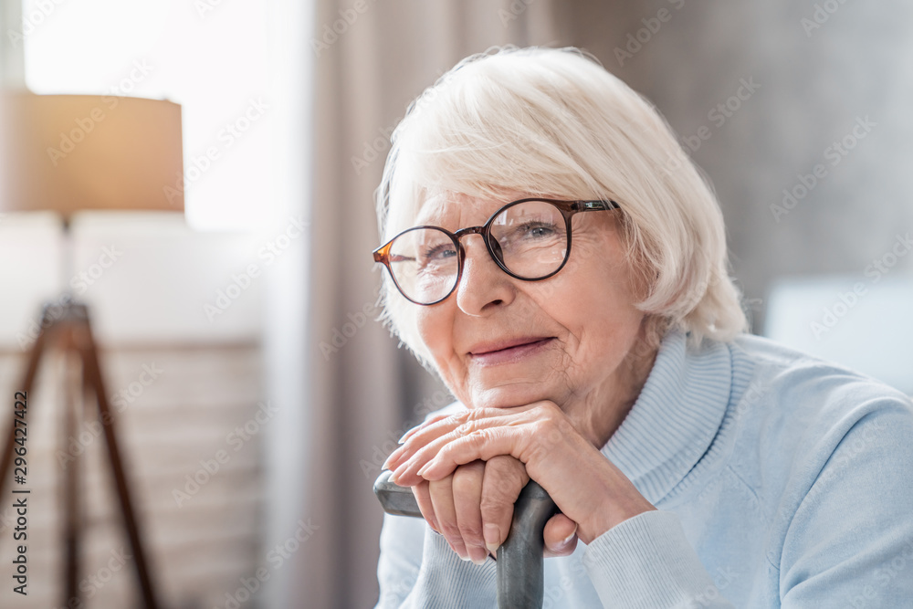 Fototapety, obrazy: Close up of mature woman in glasses holding cane while sitting on sofa at home