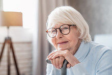Close Up Of Mature Woman In Glasses Holding Cane While Sitting On Sofa At Home