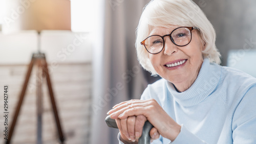 Portrait of happy mature woman in eyeglasses holding cane while sitting on sofa at home