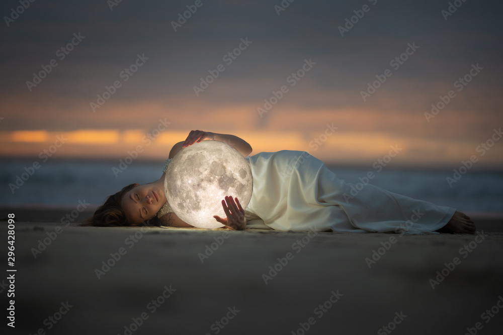 Fototapety, obrazy: Astrology. Secret and riddle. Beautiful attractive girl on a night beach with sand hugs the moon, art photo.