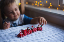 Child Boy Playing With Red Toy Christmas Train On White Knitted Plaid In Daylight With Warm Garland Bokeh Background