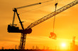 silhouette workers working on cranes on construction sites at sunset.