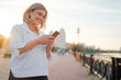 canvas print picture - Attractive young woman using smartphone while walking down the city promenade.
