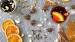 christmas and seasonal drinks concept - snowing over hot mulled wine, orange slices, raisins with cashew nuts and aromatic spices on grey background