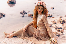 Beautiful Young Woman In Boho Dress And Wreath On The Beach At Sunset