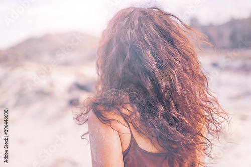 close up portrait of young woman from the back outdoors at sunset