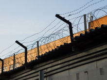 Barbed Wire Over A High Fence Against The Sunset Sky. The Theme Of Prison, Lack Of Freedom, Totalitarian Ruling Regimes