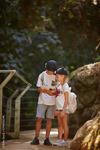 Full length boy and girl with backpacks standing on path near rocks and reading book together during trip in nature