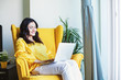 Young Indian woman using her laptop at home while sitting on a yellow armchair