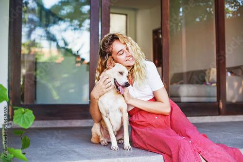 Fototapeta Beautiful caucasian woman hugging her mongrel dog pet in front of her house
