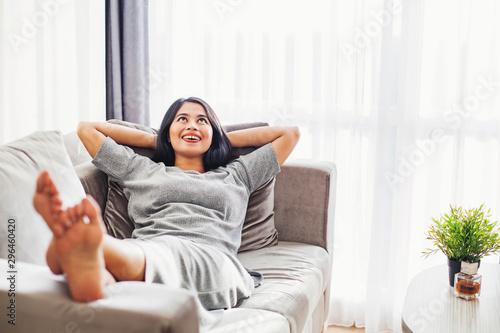 Obraz Pretty young asian woman relaxing on a sofa alone - fototapety do salonu