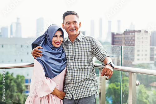 Fotomural  Happy Indonesian couple hugging on a balcony over Jakarta city view