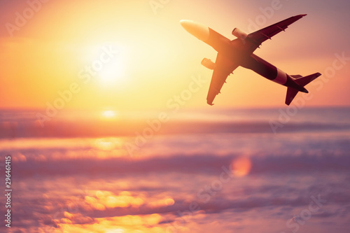 Airplane flying over tropical beach with smooth wave and sunset sky abstract background Canvas-taulu