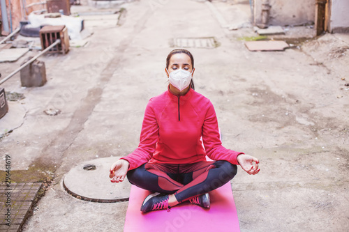 Fotografie, Obraz Woman wearing protection mask and meditating in polluted city
