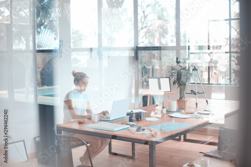 Photo  Abstract photo of a woman working on her laptop, taken through the glass