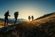Leinwandbild Motiv Group of hikers walks in mountains at sunset