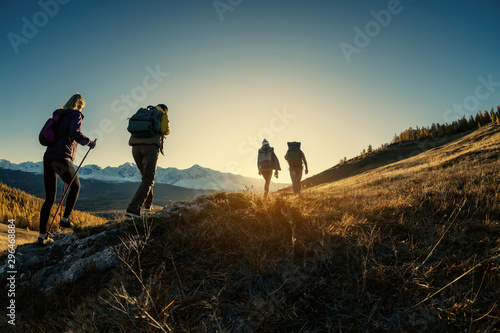Obraz Group of hikers walks in mountains at sunset - fototapety do salonu