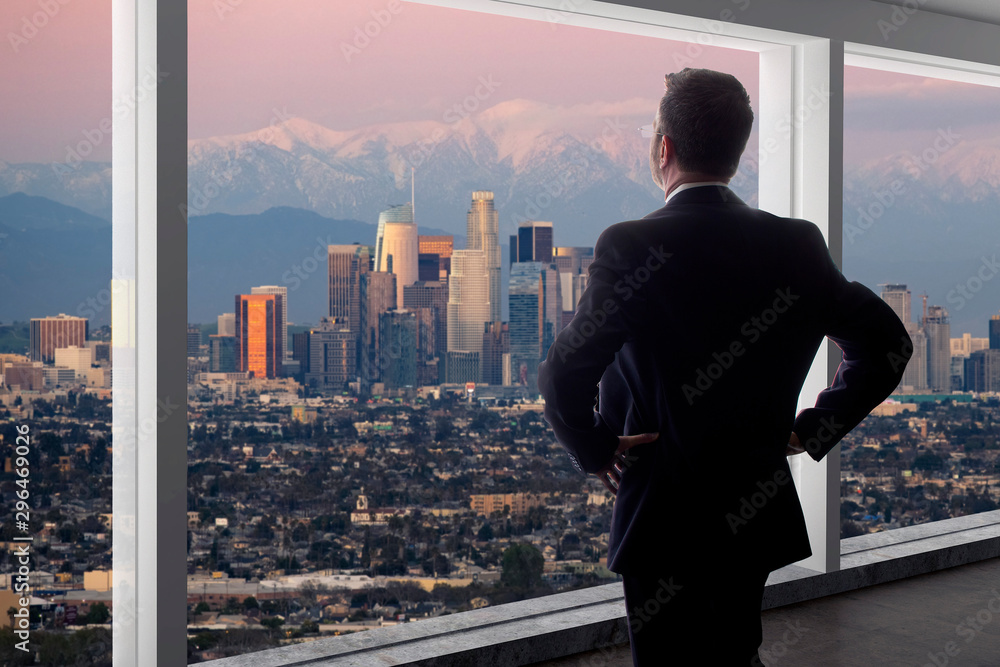 Fototapeta Businessman looking at the buildings of downtown Los Angeles from an office window.  The man looks like a politician like a mayor, or an architect or a real estate developer working in LA.