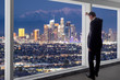 Businessman looking at the buildings of downtown Los Angeles from an office window. The man looks like a politician like a mayor, or an architect or a real estate developer working in LA.