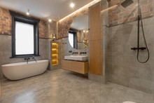 Loft Interior Of Spacious Wet Room With Bathtub Near Window And Open Walk In Shower Beside Cabinet And Sink With Mirror Against Decorated Built In Shelves On Gray Marble