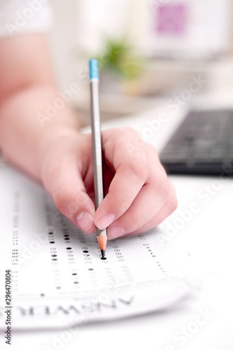 Picture of man filling OMR sheet. - 296470804