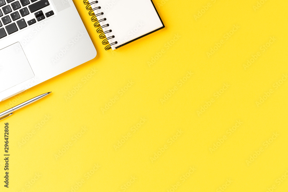 Fototapety, obrazy: Elegant office desktop with laptop, notebook and pen on yellow background with copyspace. Modern workspace