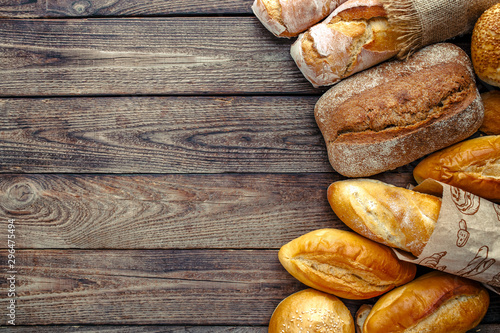 Assortment of baked bread on wooden table background,top view Wallpaper Mural