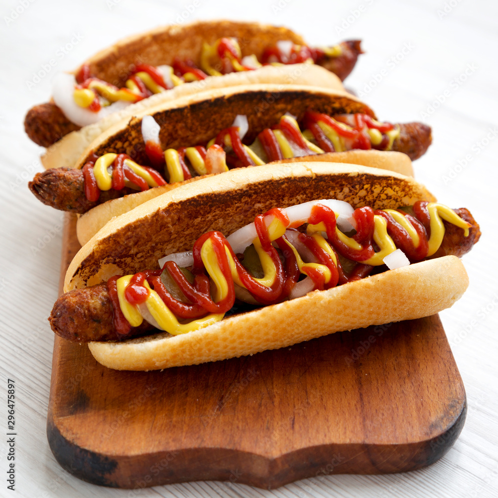 Fototapety, obrazy: Homemade hot dogs with chicken sausage, ketchup and mustard on a rustic wooden board on a white wooden surface, low angle view. Close-up.