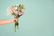 canvas print picture - Female hand with bouquet of beautiful flowers on color background