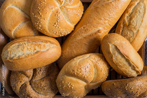 Fotobehang Brood Bread and lots of fresh bread buns in a basket on a wooden table