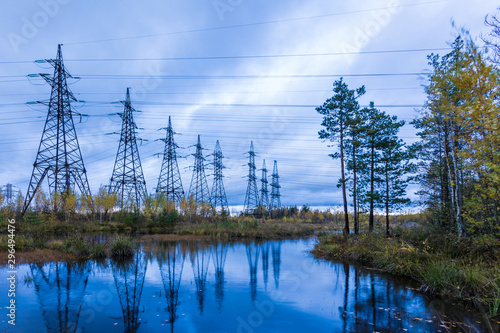 Towers of electric main with the wires in the autumn countryside swamp on the ba Canvas Print