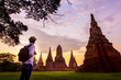 Leinwanddruck Bild - Young man travel in Ayutthaya Historical Park at Wat Chaiwatthanaram where UNESCO World Heritage Site