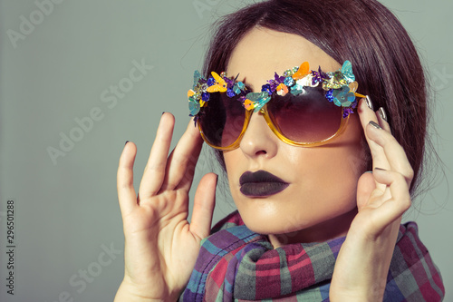 Portrait of fashioned woman in stylish sunglasses and colorful scarf
